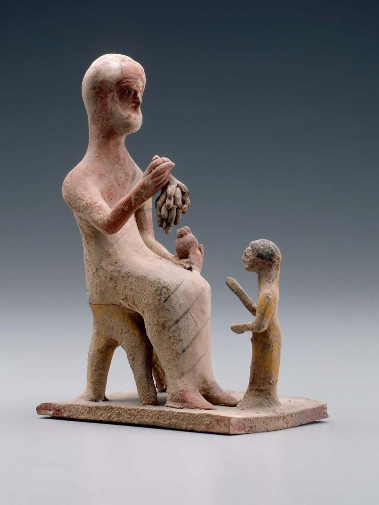Statuette of an old man offering grapes to a girl.  Grandfathers were important figures in Greek families, as we know from ancient literary sources and inscriptions on grave stelai. This rare late archaic Greek sculpture shows an old, white-haired and partly bald man offering fruit to a small girl. Significant amounts of pigment are preserved on both figures, reminding us that most Greek sculpture was originally painted. Here close looking reveals details of the elegant textiles used to make the elder's clothing. Such details confirm his status as the grandfather. Terracotta group sculpture in the Museum of Fine Arts, Boston inv. no. 97.350, ca. 500-475 B.C.