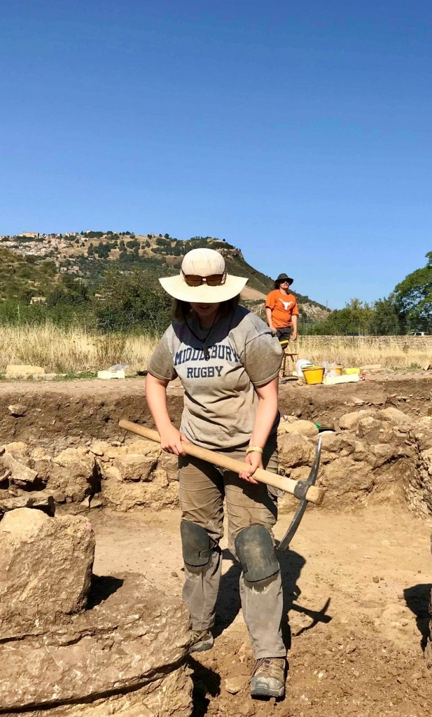 A picture of the author hold a large pick axe while on excavation in Sicily.