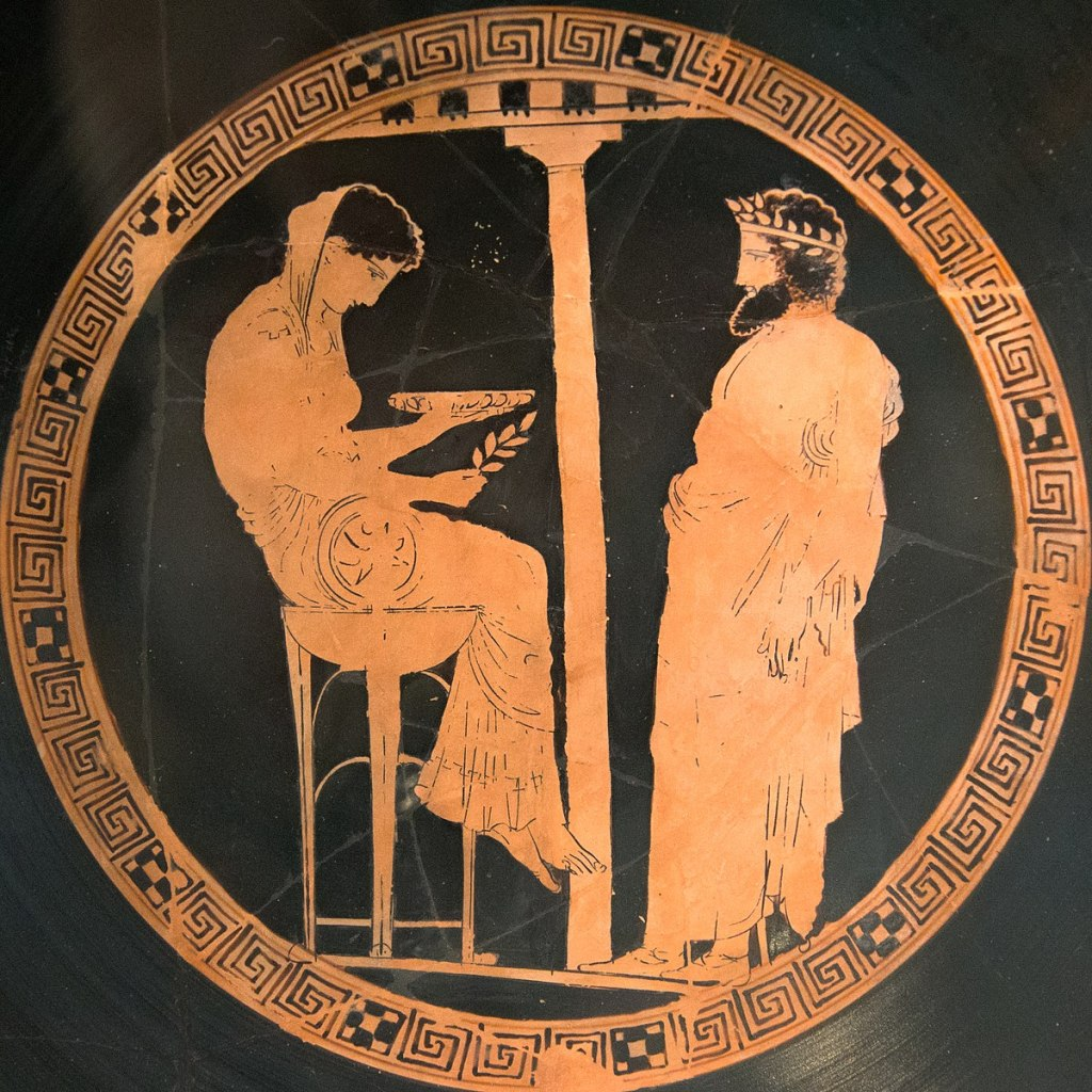 Close-up of an Attic red-figure vase with the seated Pythia on the left and King Aigeus on the right.