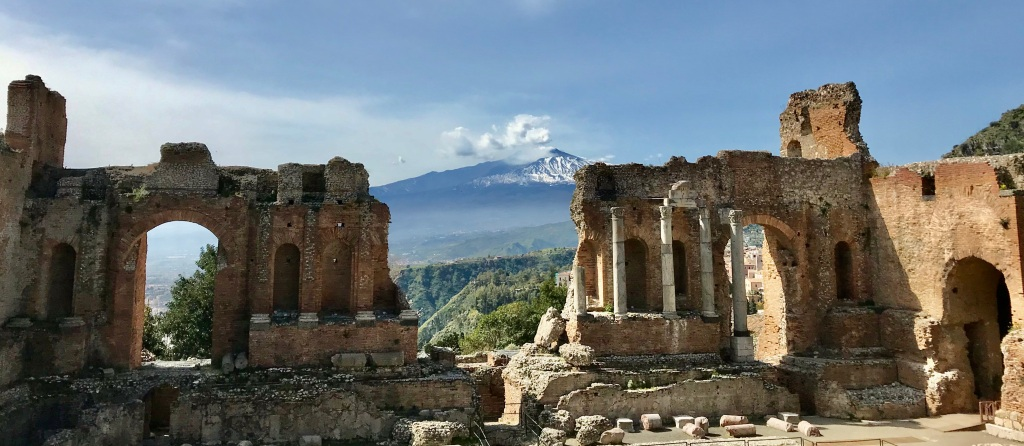 The ancient theater of Taormina in the foreground with Mt. Etna giving off smoke in the distance.
