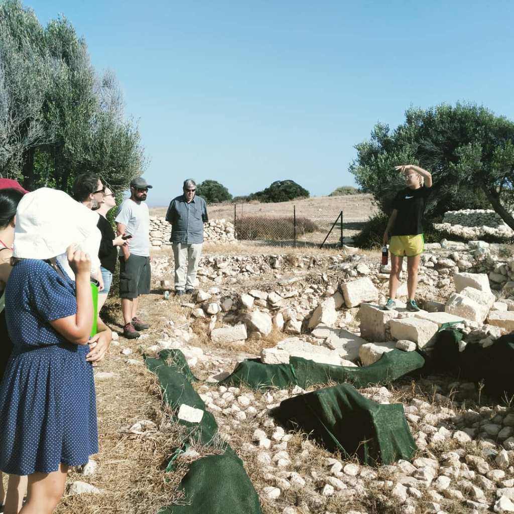 Amanda explaining architectural destruction and ongoing excavation at Kourion in Cyprus.