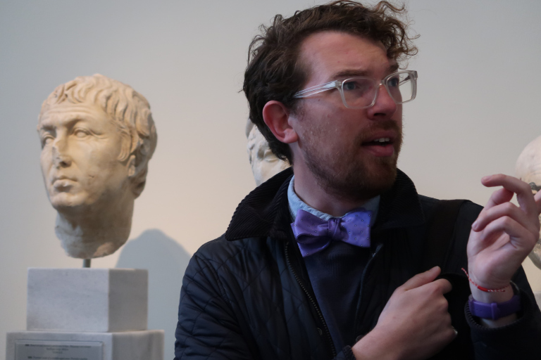 Image of Dr. Dylan Rogers talking in front of a marble head in a museum.