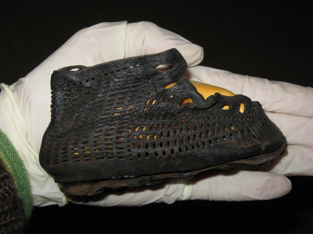A small leather shoe for a baby, with a distinct fishnet pattern.