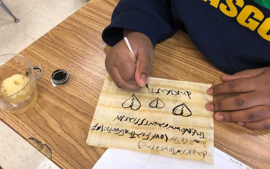 Image of student writing with squid ink on papyrus.