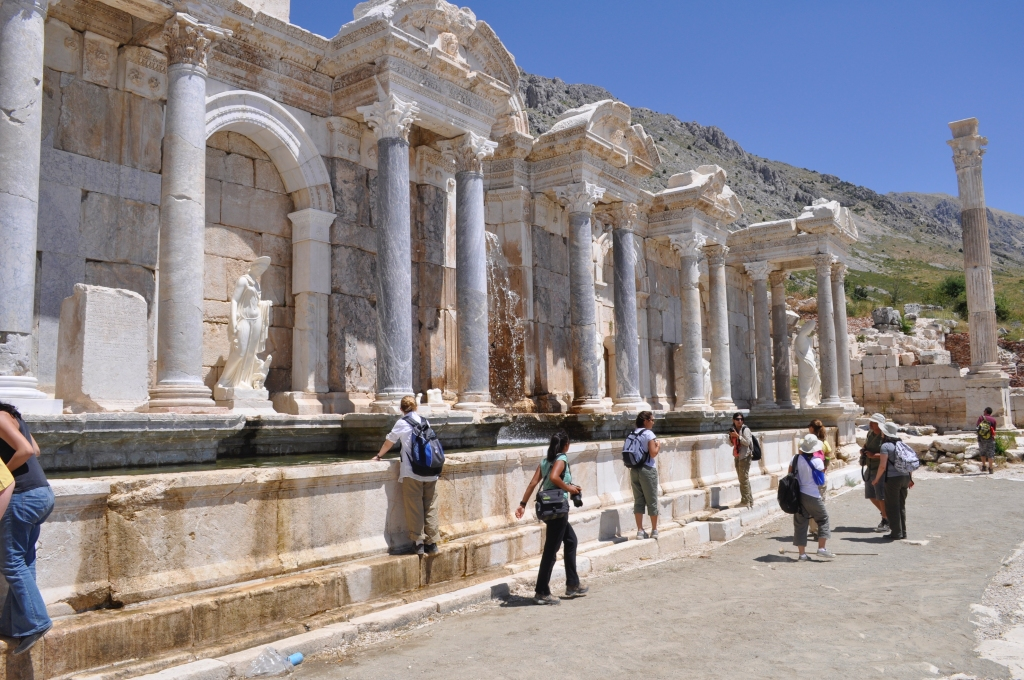 Image of the Antonine Nymphaeum at Sagalassos, Turkey with tourists waslking in front of the structure.