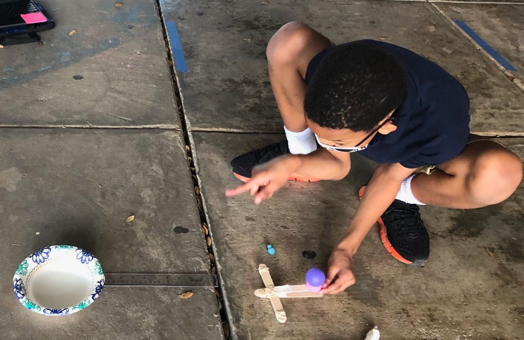 Student trying to launch a mini ball from a mini-catapult into a bowl.