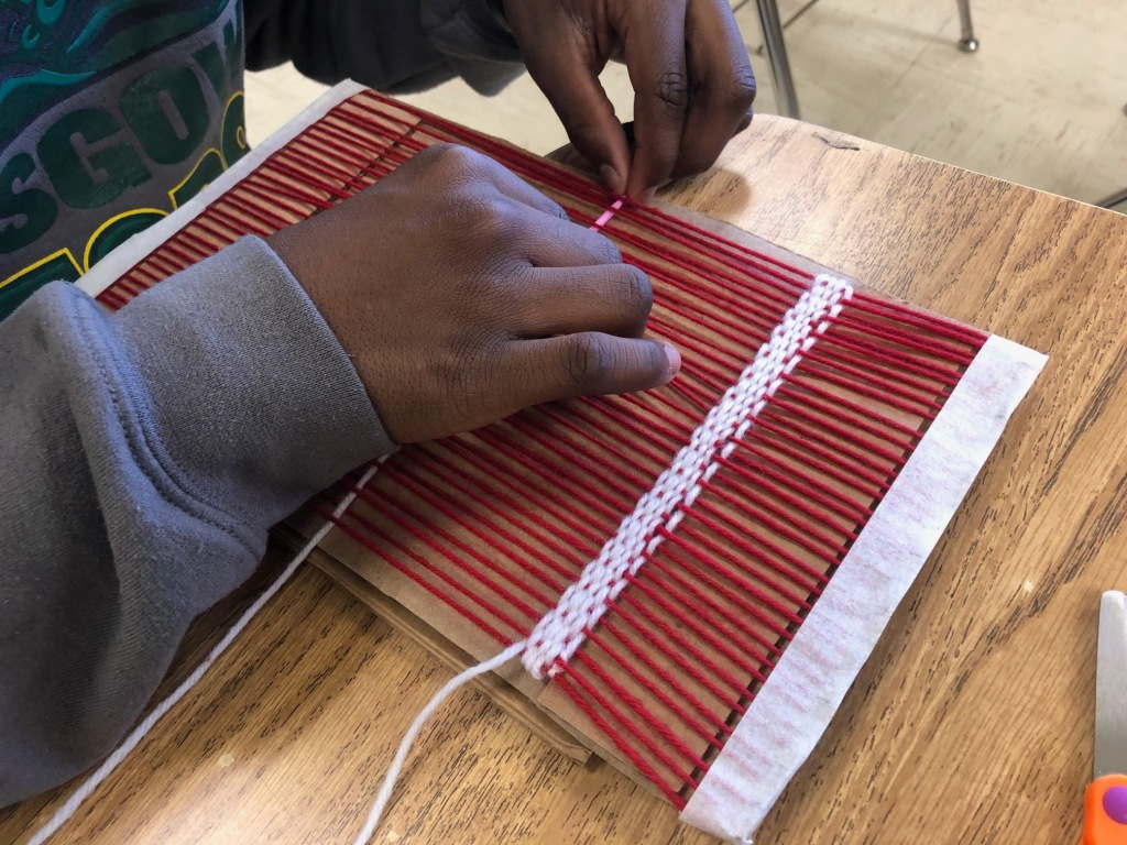 Image displaying the hands of a student trying out a cardboard loom
