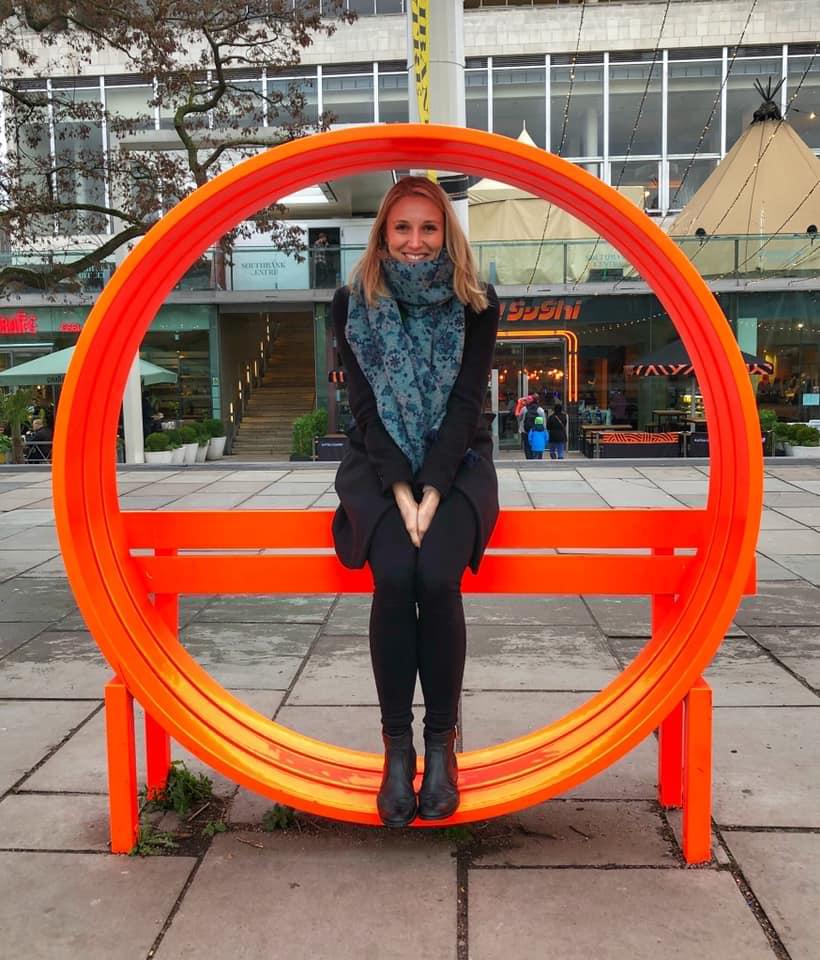 Photo of Dr. Victoria Austen sitting inside an orange circular art installation.