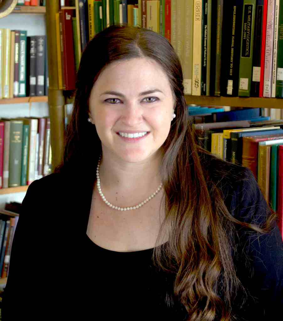 Headshot of Dr. Liana Brent in front of a bookshelf.