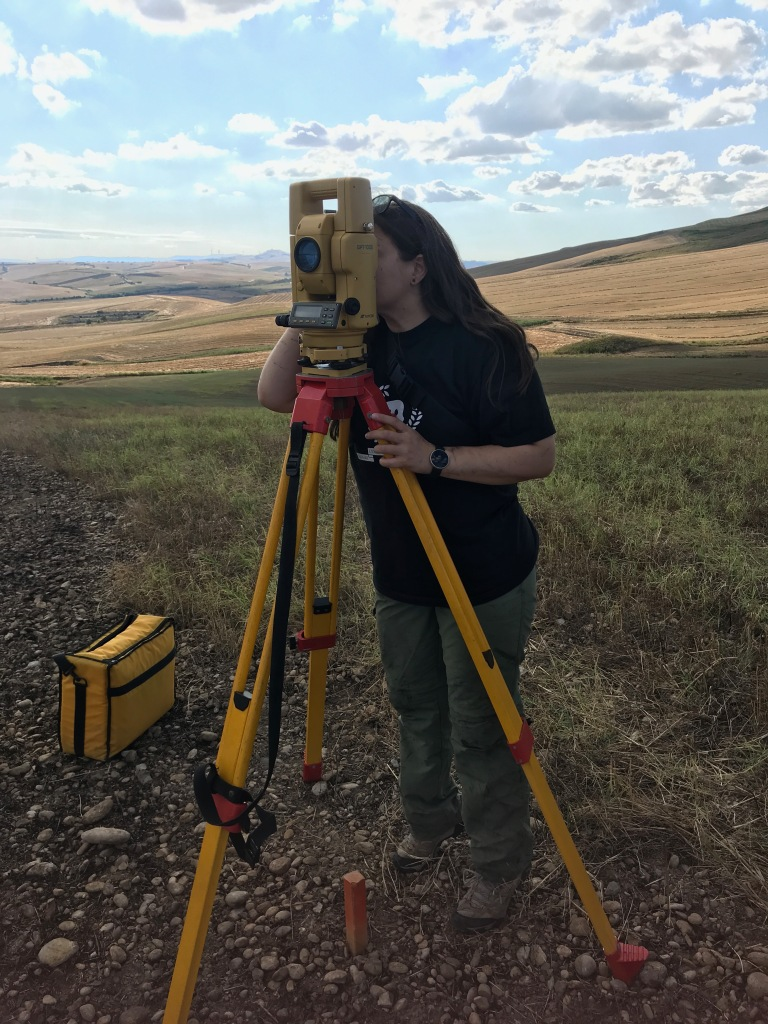 Dr. Liana Brent surveying while looking into a total station.