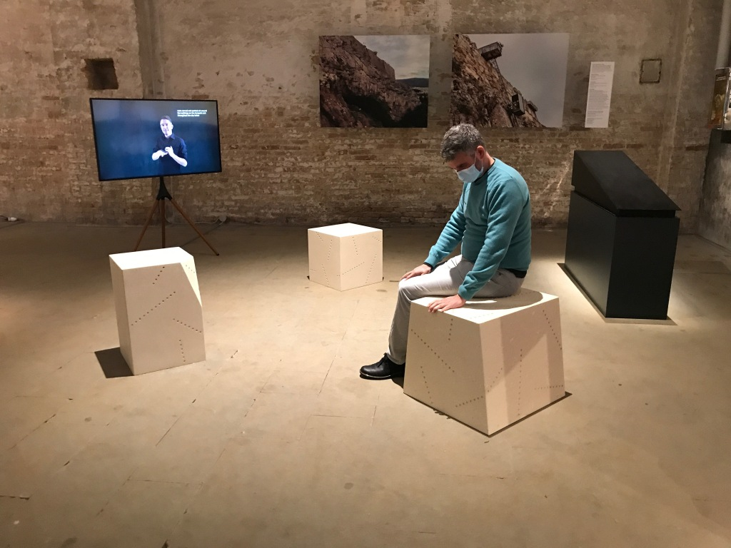 A man wearing a mask sits on one of three stone seats, touching its pattern of drilled holes. In front of the seats a monitor and stand display the image of a man performing in sign language. On the wall are photographs of the rock of the Acropolis in Athens and a rickety elevator. Behind the man stands a black, vibrating model of a ramp.