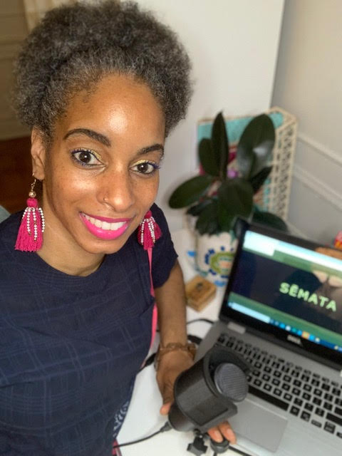 """A woman with dangling pink earrings and pink lipstick sits at her desk holding her microphone in front of her laptop with the title of the film """"Sēmata"""" on the screen. A plant is visible on her desk in the background."""