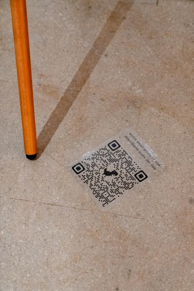 A QR code with a small dinosaur at its center is labeled with Audio Description of Film in English and Italian.