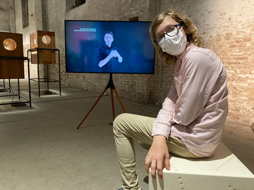 A boy wearing glasses and a face mask, seated on a stone with a pattern of holes drilled into it to evoke the weathering of rock, in front of a monitor on a wooden easel in which a man performs in sign language.