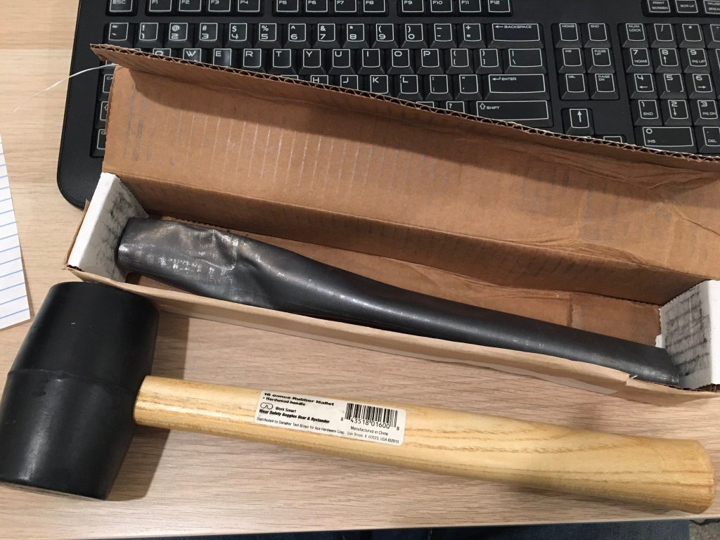 A modern lead curse tablet in a box with a mallet in front of it.