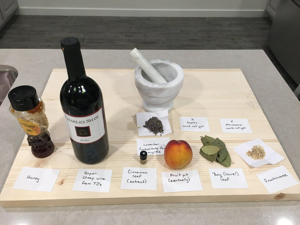 A collection of modern items used to make incense displayed on a table. These include wine, honey, lavender, bay leaves and frankincense.