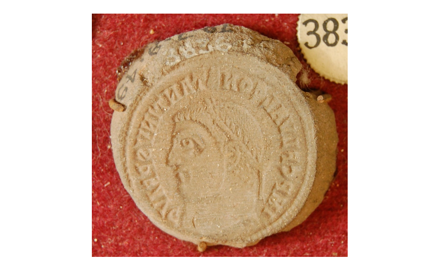 A coin mould made from red ware pottery with the edges chipped around the top. The coin mould displays a profile view of Constantine I with the inscription: IMP C FL VAL CONSTANTINVS P F AVG.