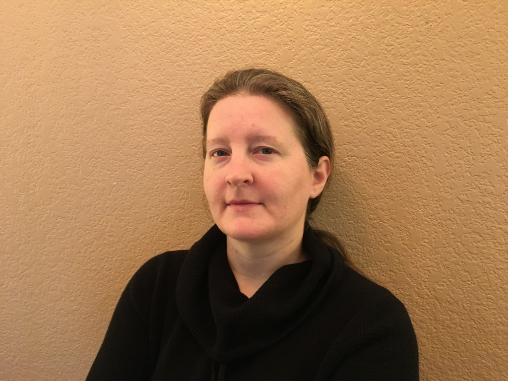 A headshot of Dr. Britta Ager against a beige background