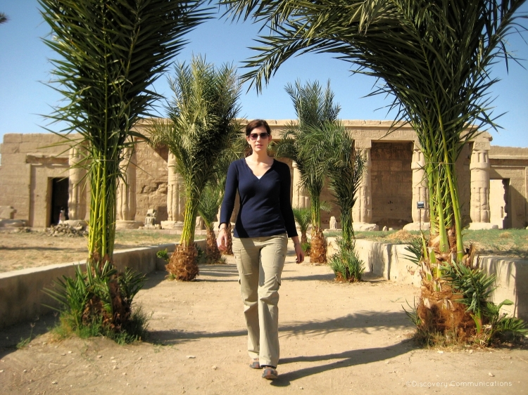 Dr. Kara Cooney walks towards the camera in front of a temple in Egypt