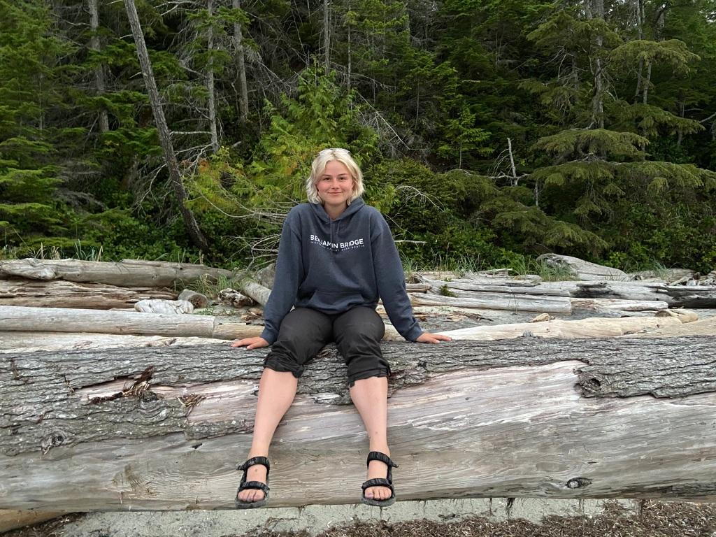 Lauren Millet sitting on top of a fallen tree.