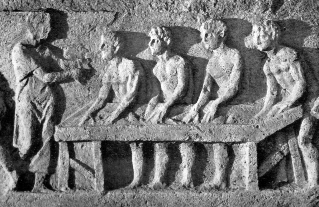 Relief from the Tomb of Eurysaces in Rome depicting 4 men shaping loaves of bread, while another man oversees their work to the left of the scene.