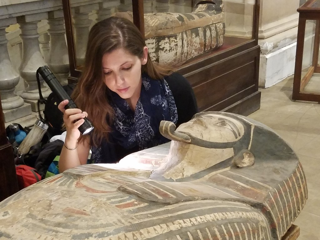 Dr. Danielle Candelora examining an Egyptian mummy coffin with a flashlight in a museum.