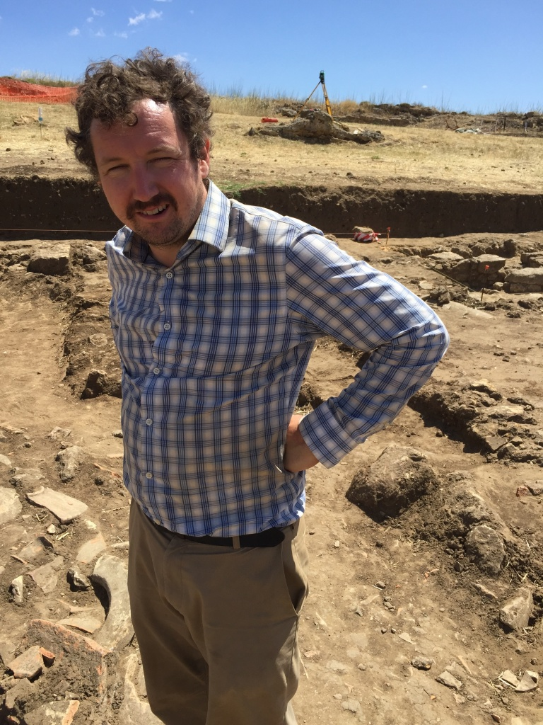 Dr. Jared Benton standing in the middle of an excavation trench.