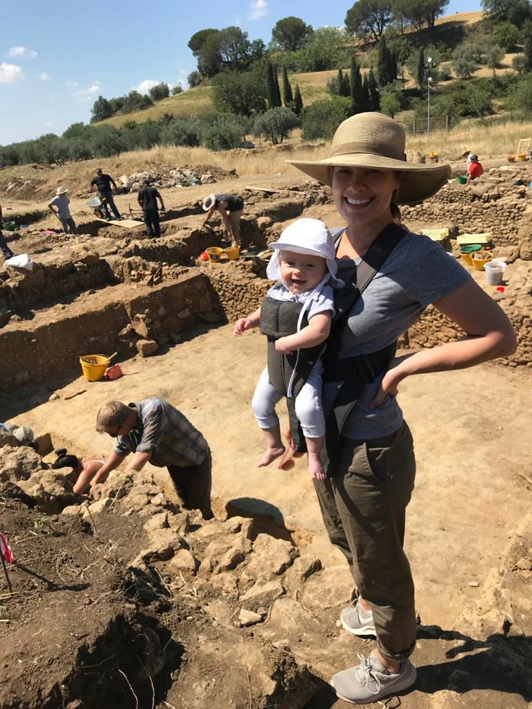 Dr. Katherine Huemoller on excavation standing in a trench with her child strapped to her chest.