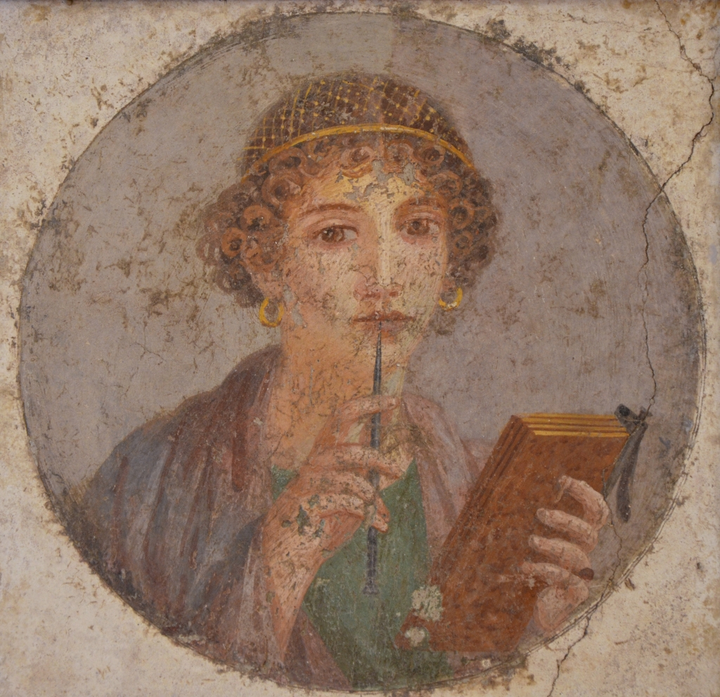 """Fresco known as the so-called """"Sappho Tondo"""" from Pompeii of a woman holding a tablet and a stylus to her lips"""