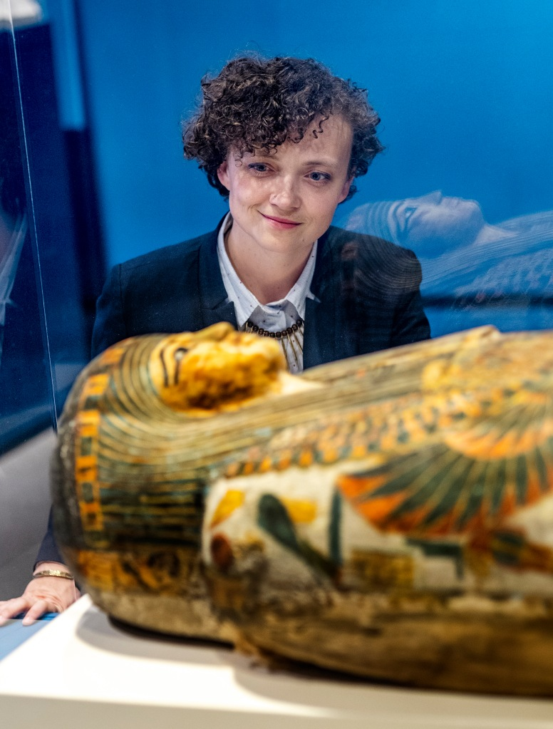 Photo of Dr. Anne Austin looking at an Egyptian sarcophagus through a glass case.