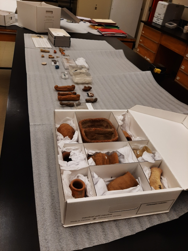Egyptians items laid out across a table, while a few remain packed inside a box.