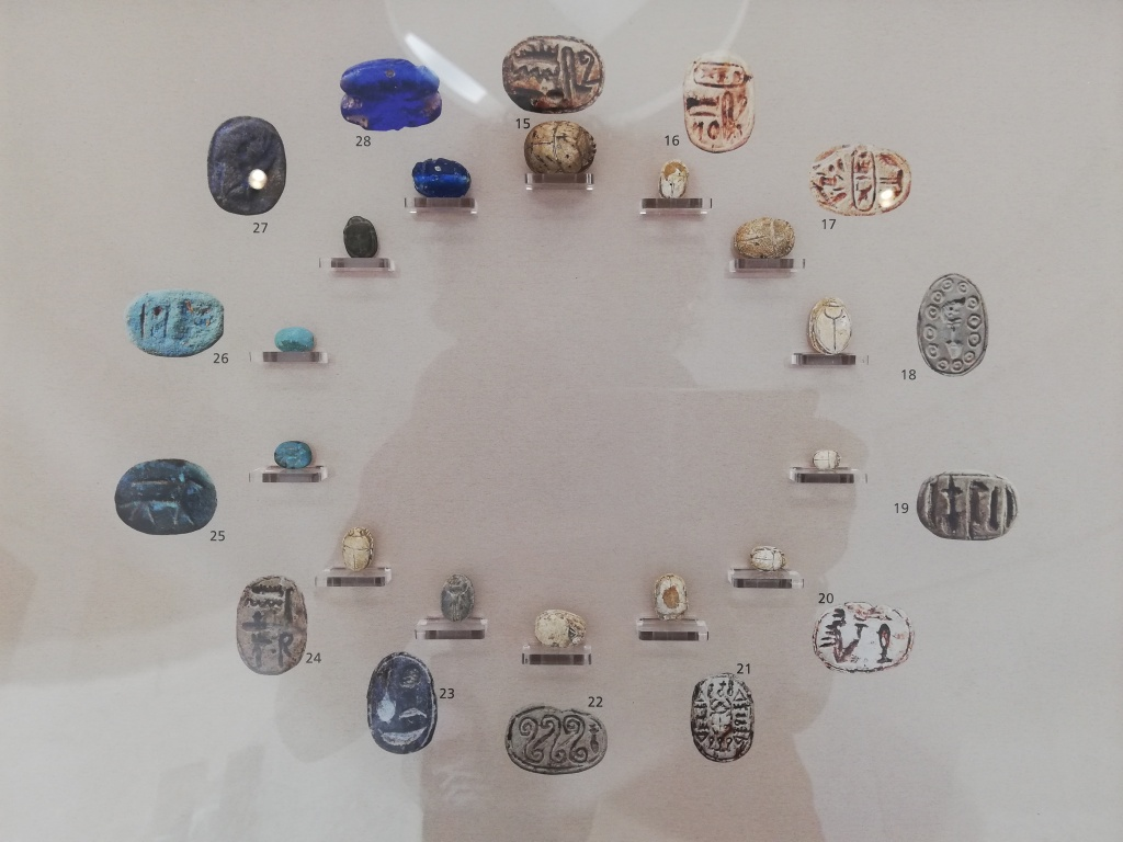 A collection of stone and faince scarabs on display (laid out in a circular fashion) in the Museo Regionale, Trapani .