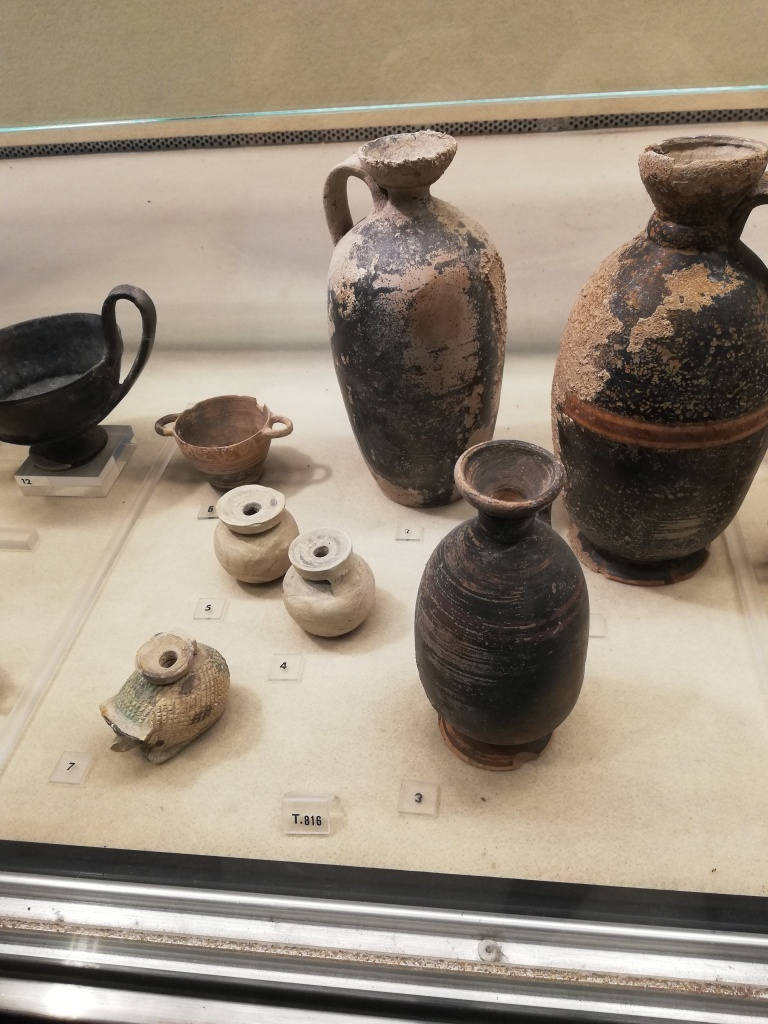 Grave goods in a museum display, include a hedgehog-shaped aryballos and three vases from the Museo Archeologico Regionale, Syracuse.