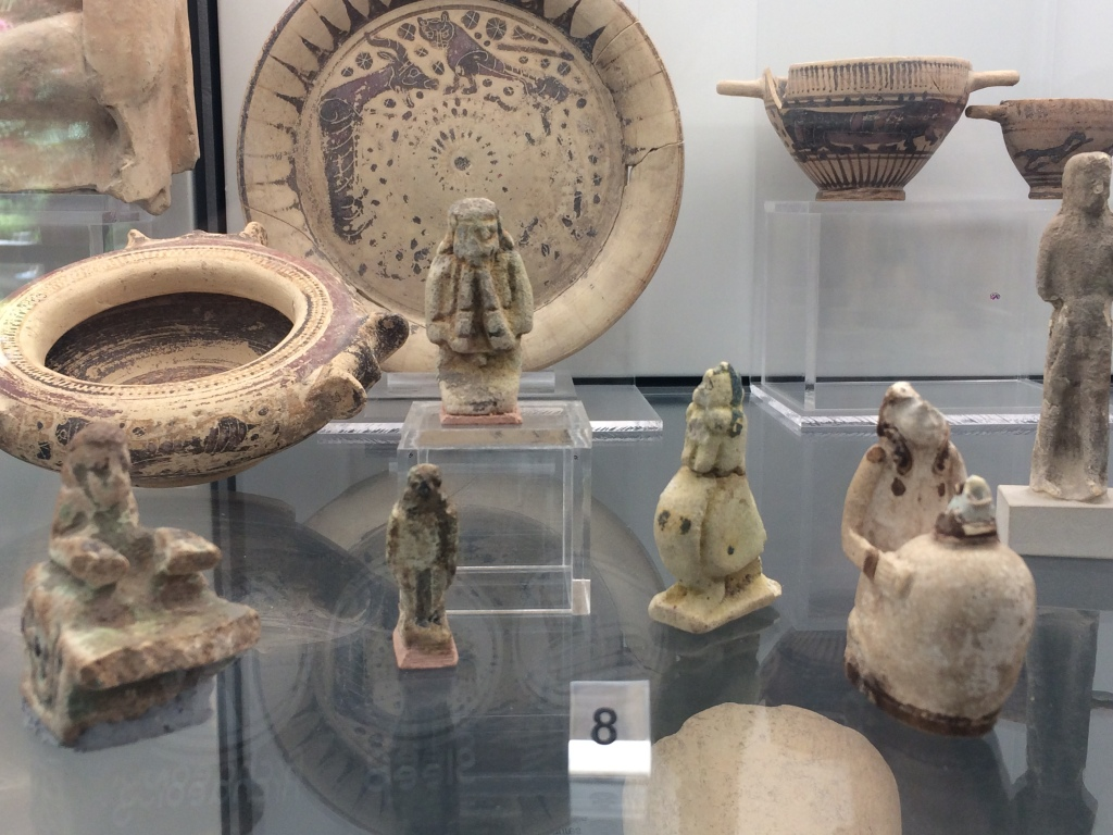 Faience figurines in a display case in the Museo Archeologico Regionale, Palermo. Here we have a flute player, rooster, and falcon, amongst other objects.