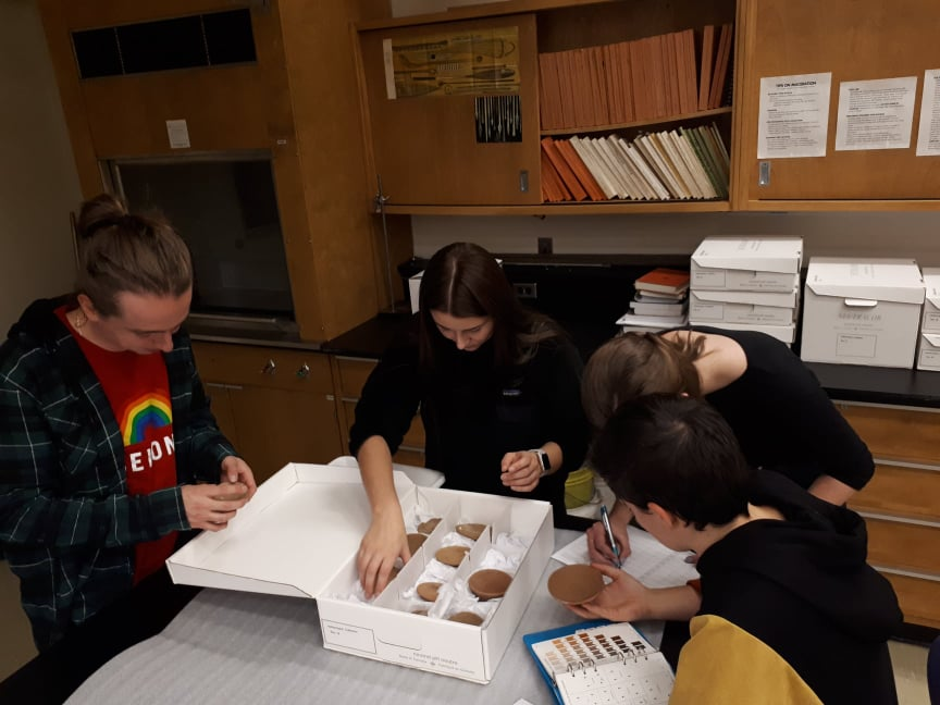 Students gathered around a box of pottery, examining the pieces.