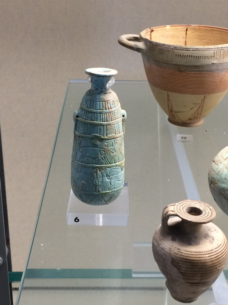 A Faience (blue) aryvallos in a museum display decorated with several incised animals from the Museo Archeologico Regionale, Syracuse.