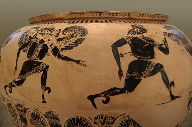 Photograph of a painted terracotta pot. It is a close-up of one side of the pot, where figures painted in black are running. A winged Gorgon with profile legs and arms but frontal face and torso runs after a man with profile face, legs, and head, but frontal torso. Both are wearing tunics and winged sandals. There is decorative black-painted ornaments above and below.